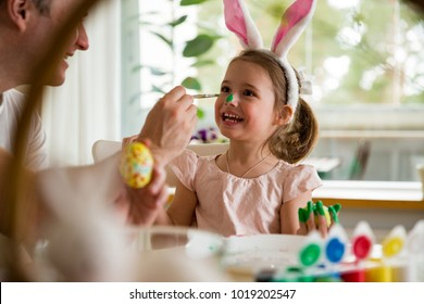 A father and daughter celebrating Easter, painting eggs with brush. Happy family smiling and laughing, drawing on face. Cute little girl in bunny ears preparing the holiday.