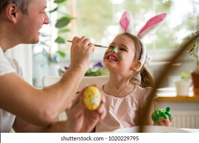 Een vader en dochter vieren Pasen, eieren schilderen met penseel. Gelukkige familie glimlachend en lachend, tekenen op gezicht. Schattig klein meisje in konijnenoren de voorbereiding van de vakantie.