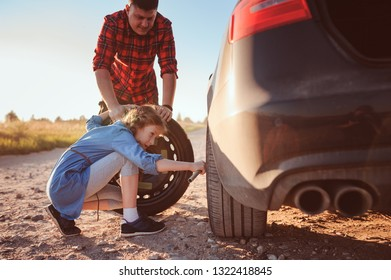 father and daughter changing broken tire during summer rural road trip. Kid helping to fix problems with car