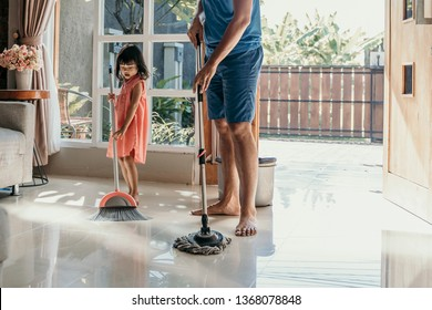 father and daughter clean up the house together sweep the floor