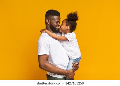 Father and daughter connection. Positive black man and little girl touching noses, cuddling on orange studio background