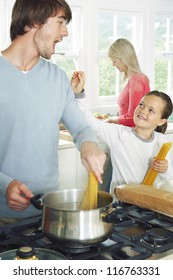 Father and daughter cooking spaghetti in the kitchen with the young girl playfully trying to feed him an uncooked strand