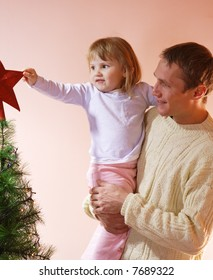father and daughter decorate christmas tree