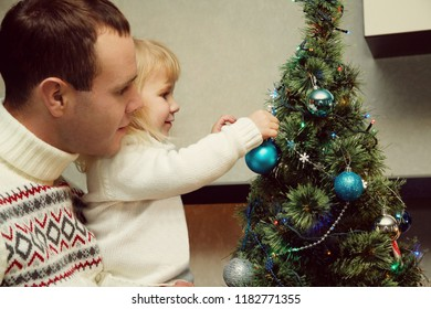 father and daughter decorating a Christmas tree with blue balls