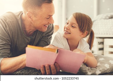 Father and daughter. Delighted positive cheerful girl looking at her father and smiling while reading a book with him