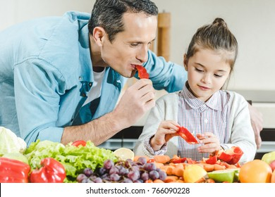 father with daughter eating pepper together at kitchen