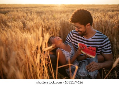 Father and daughter eating watermelon in the field