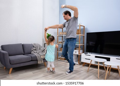 Father And Daughter Enjoying Dancing Together At Their Modern Home