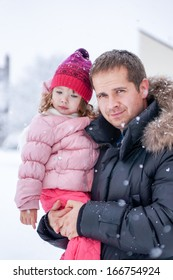 Father and daughter enjoying snow blowing at daytime