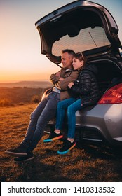 Father and daughter enjoying sunset while sitting in the car trunk at camping on a hill