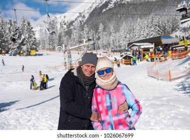 Father with daughter enjoying winter vacations over mountains background. Ski resort