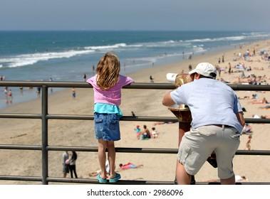 Father and Daughter Examine Coast Through Telescope