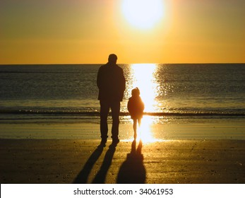 father and daughter facing the sea during sunset