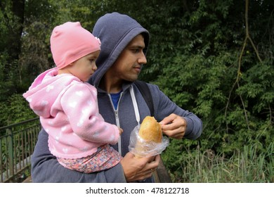 Father and daughter feeding ducks bread