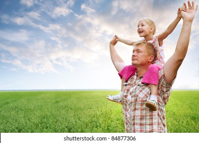 father with daughter in field hands up