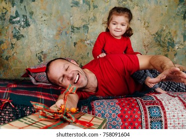 Father and daughter are fighting for a gift on the bed. A girl riding an adult tries to take a gift. New Year's Eve, family atmosphere. Red T-shirts, pajamas. Present box with a bow.