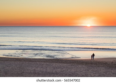 Father and daughter in a fine sand beach, close to the ocean, watching a very strong colored sunset