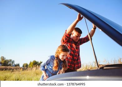 Vater und Tochter reparieren Probleme mit dem Auto während der Sommerfahrt. Kind, das Papa hilft.