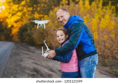 father and daughter with flying drone in the autumn park. Man with remote controller in his hands taking aerial photos and videos