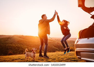 Father and daughter giving high five while camping on a hill with small yellow dog during sunset