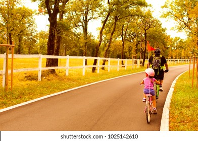 Father and daughter going in bicycle, family cyclo holidays, summertime. Family, education, recreation and sport concept.