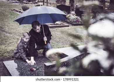 Father and daughter at graveyard visiting grave of mother