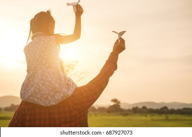 Father and daughter are happy with the paper plane on the meadow.