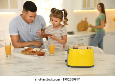 Father and daughter having breakfast at table in kitchen, focus on toaster