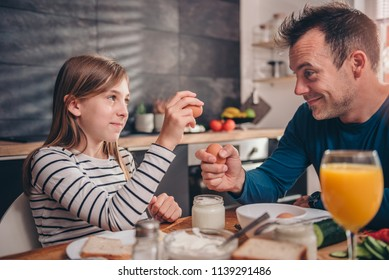 Father and daughter having breakfast together at home
