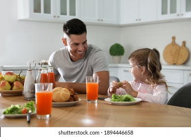Father with daughter having breakfast together at table in modern kitchen