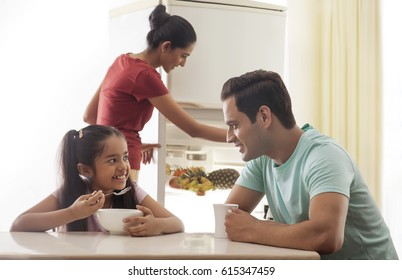 Father and daughter having breakfast while mother opening refrigerator