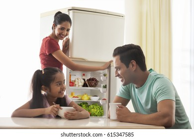 Father and daughter having breakfast while mother opening refrigerator in background