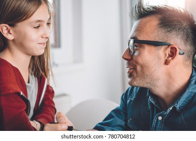 Father and daughter having conversation at home