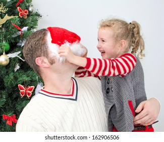 Father and daughter having fun at the christmas. Girl trying to put on Santa's hat on father.