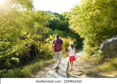 Father and daughter having fun hiking on warm and sunny summer day during family vacations in Zagoria region, Greece