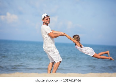 Father with daughter having fun on the beach at the day time