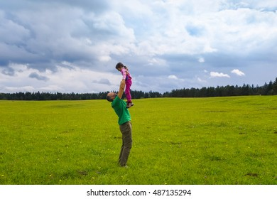 Father and daughter having fun on a beautiful day. Devoted father holding his daughter. Family active lifestyle concept.