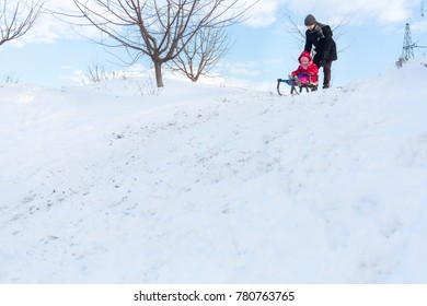 Father and daughter having fun on winter day. Girl sledding on snow.