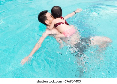 Father and daughter having fun in the pool. Summer holidays and vacation concept