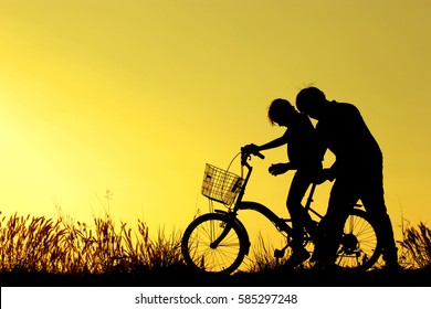 father and daughter having fun riding bike at sunset, active family sport, active kids sport, Asian kid,Silhouette a kid at the sunset