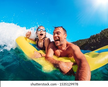Father and daughter having fun in the sea and getting splashed by the big waves while floating on the inflatable yellow airbed