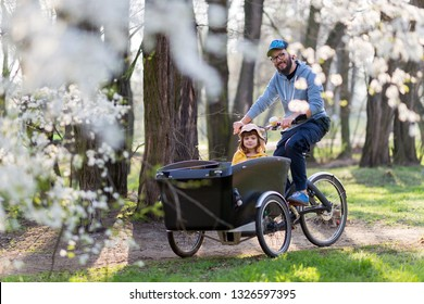 Father and daughter having a ride with cargo bike during spring