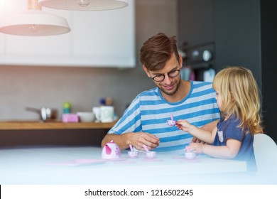 Father and daughter having a tea party at home