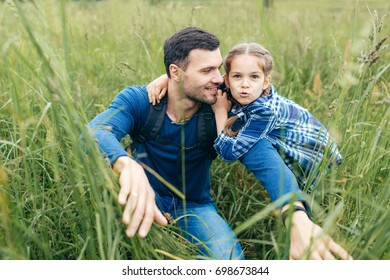 Father with daughter having walk on green grass, enjoying every moment of being together. Little playful kid embracing her father who is paving way in high grass, looking at her daughter with love