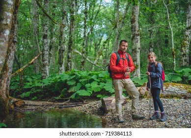 Father and daughter hiking in forest and posing by the small mountain stream