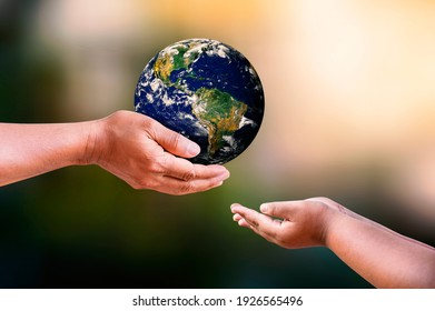 Father and daughter holding earth in hands on blur nature backgrounds. Earth day concept. Elements of this image furnished by NASA.