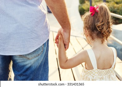Father and daughter holding hand in hand at sunset