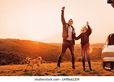 Father and daughter holding hands and jumping at camping on a hill with small dog during sunset
