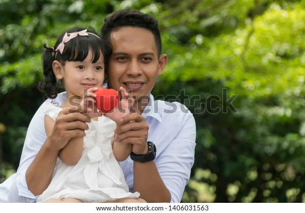 Father and daughter holding heart shape soft toy, healthy family concept