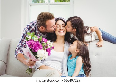 Father and daughter kissing mother sitting on sofa at home